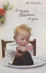 A HAPPY CHRISTMAS TO YOU  young child sits behind Xmas pudding topped with flag