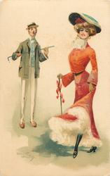 woman in red with large hat, monocled man holds cane across chest with both hands