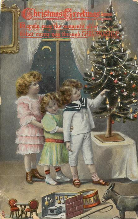 CHRISTMAS GREETINGS or  A HAPPY CHRISTMAS two girls and young boy line up on left of Xmas tree, toys front