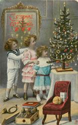 CHRISTMAS GREETING  two girls and young boy in a line, Xmas tree right, toys & chair front