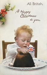 A HAPPY CHRISTMAS TO YOU  child sits behind Xmas pudding topped with flag, holly