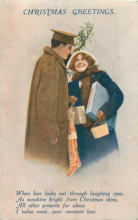 CHRISTMAS GREETINGS  soldier holds mistletoe over smiling girl