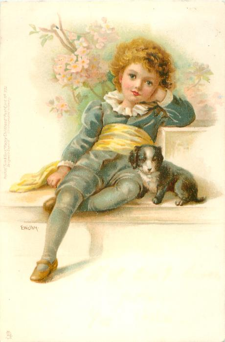 boy in blue/green suit sitting with puppy