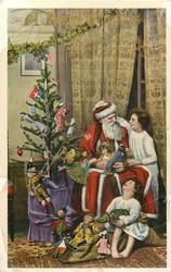 A HAPPY CHRISTMAS  tree left, Santa seated and girl has right arm around his neck, girl at his feet cranes neck to watch, golly