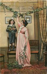 A MERRY CHRISTMAS  boy stand on chair, woman reaches up to hang mistletoe