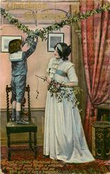CHRISTMAS GREETINGS  boy stands on chair adjusting mistletoe, woman holds holly