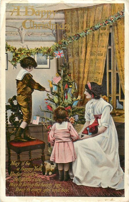 A HAPPY CHRISTMAS  mother right sitting, small girl next to her faces away, boy standing on chair, tree in centre