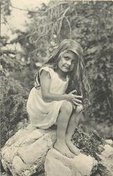 barefoot young girl sitting on rock, facing right, looking front & up
