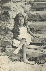 barefoot young girl sitting on stone step, legs crossed, two boards under her, left hand on step