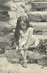 young girl sitting on stone step, legs crossed, putting on a sock