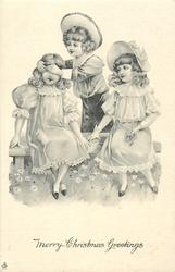 two girls sit on bench, boy stands behind with hans over one girls eyes