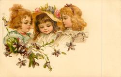 three girls, middle girl wears hat with roses, violets below