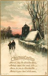 CHRISTMAS GREETINGS  man & woman walk front on snowy road, lighted church back right