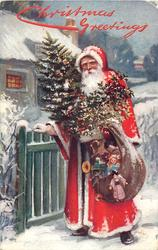 Santa carrying sack of toys & tree stands with hand on gate