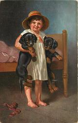 child in night clothes holding two dachshunds