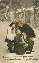 A HAPPY CHRISTMAS  2 girls & boy in snow in the street, one girl holds holly