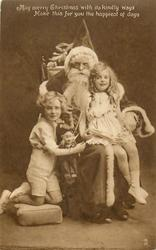 MAY MERRY CHRISTMAS  ... boy & girl on either side of seated Santa, puppet dangles