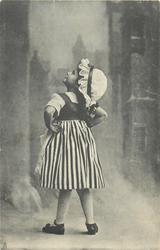 girl in vertically striped skirt faces away & looks up