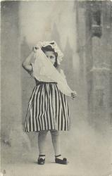 girl in vertically striped skirt faces front holds apron partly in front of face