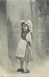 girl in vertically striped skirt stands facing left