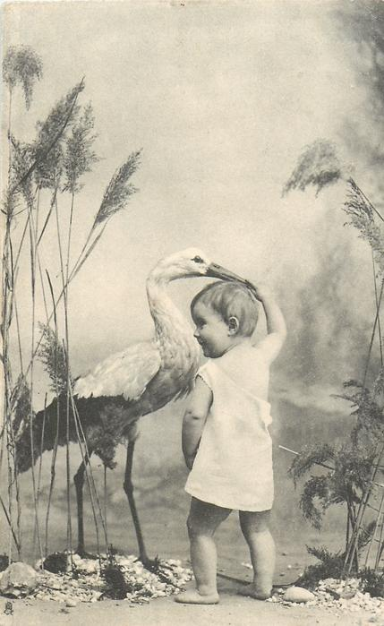 stork left, baby stands right looking left, one hand by his side the other holds birds bill