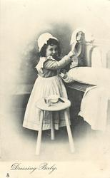 DRESSING BABY  girl stands, doll on bench to right