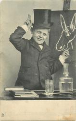 boy dressed in long coat and top hat with glasses, points to donkey on blackboard  with left hand, two fingers of right hand point up