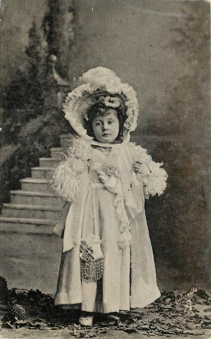 young girl in very elaborate dress and bonnet stands in front of steps