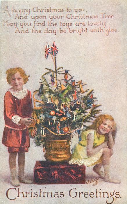 CHRISTMAS GREETINGS  boy & girl on each side of Xmas tree