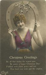 CHRISTMAS GREETINGS  girl looking front holding horseshoe above her head, mistletoe