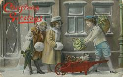 CHRISTMAS GREETINGS  young boy right has wheelbarrow with vegetable, he offers it to two girls, girl left holds umbrella