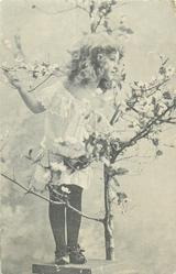 pose of small girl standing on pedestal with her right arm held up touching twig, left hand holds blossom tree trunk, she faces front but kooks right
