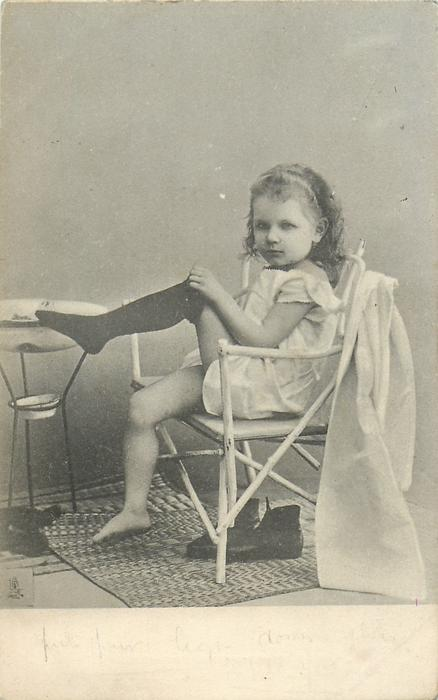 young girl in nightdress, sitting in chair, has one stocking  on, washbowl in front of her