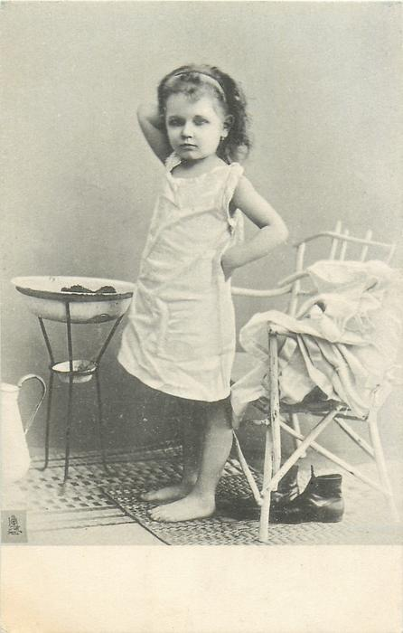 young girl in nightdress, standing in front of chair with clothes on it, wash bowl in front of her
