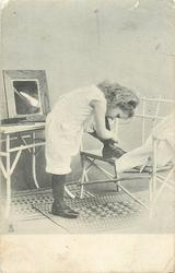 young girl in underclothes has one foot up on chair whilst she adjusts lace, mirror on table left