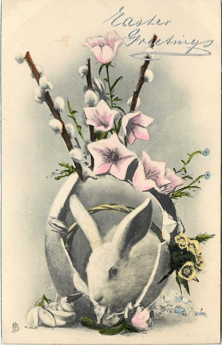 white bunny in egg with pink morning glories, white pussy willows and small blue forget-me-nots