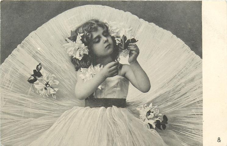 girl with enormous skirt holds a flower up front of her with one hand & peers at it
