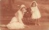 girl stands to right of pekingese in pram, mother sits on ground front left