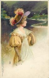 girl in golden dress, white throw, wide brimmed hat with feathers, sky & water behind nearly black