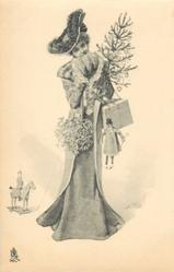 girl stands holding christmas tree, mistletoe, puppets & box