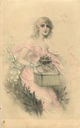 woman seated on flowery bank holding bird's nest above box