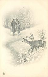 snowy woods with man and woman walking through, two deer behind