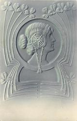 art nouveau style profile of ladies head looking right, surrounding decoration with 3 leaf clover
