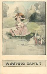 A JOYOUS EASTER  girl sits on grass observed by  two fairies from behind a stone