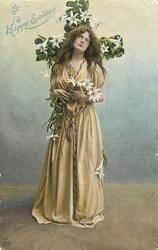 A HAPPY EASTER  woman stands in front of flowered cross clasping lilies, faces front