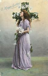 A HAPPY EASTER  woman stands in front of flowered cross clasping lilies, faces left