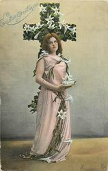 EASTER GREETINGS  woman stands in front of flowered cross clasping lilies, has book in hand