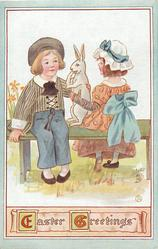 EASTER GREETINGS  boy & girl sit on bench with large rabbit between them