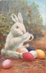 bunny with paws out, red eyes, facing right, coloured eggs on ground