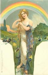 woman with long hair, has both hands on hair, blue cloak over left arm